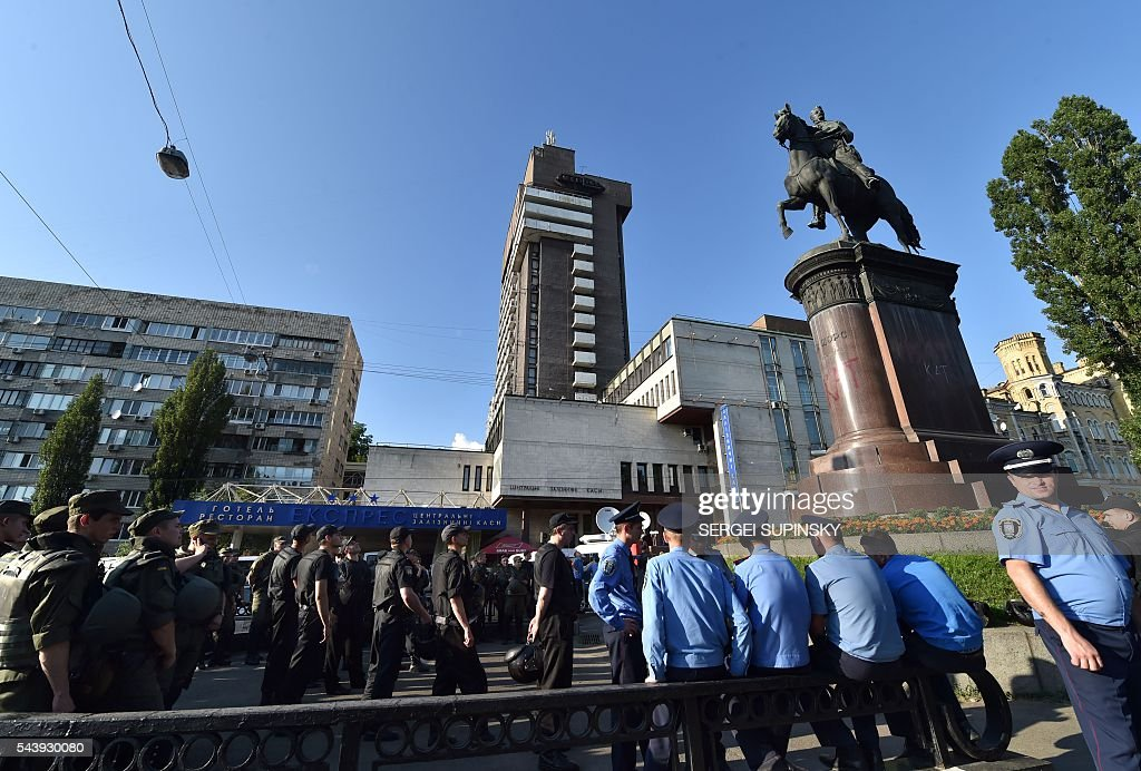 Hundreds of policemen guard a Soviet era monument for Bolshevik and Red Army commander Nikolai Shchors to prevent it dismantling in the centre of Kiev on June 30, 2016. Activists of some nationalists parties and the movements accused the Kiev city government of inaction in the implementation of the Decommunisation Law and were going to destroy the monument of the 'butcher of Ukrainian people'. The monument to Red Divisional Commander of the Bolshevik Revolution and the Civil War in 1917 was opened in 1954 to mark the 300th anniversary of the reunification of Russia and Ukraine. / AFP / SERGEI