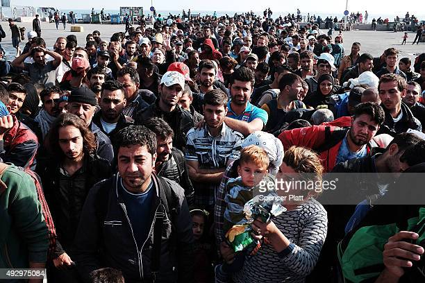 Hundreds of recently arrived migrants wait to board a ferry to Athens on October 16 2015 in Mytilene Greece Dozens of rafts and boats are still...