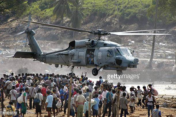 Hundreds of residents of Calang town flock under a US helicopter as volunteers distribute food in Aceh Jaya in the tsunamiravaged western Aceh coast...