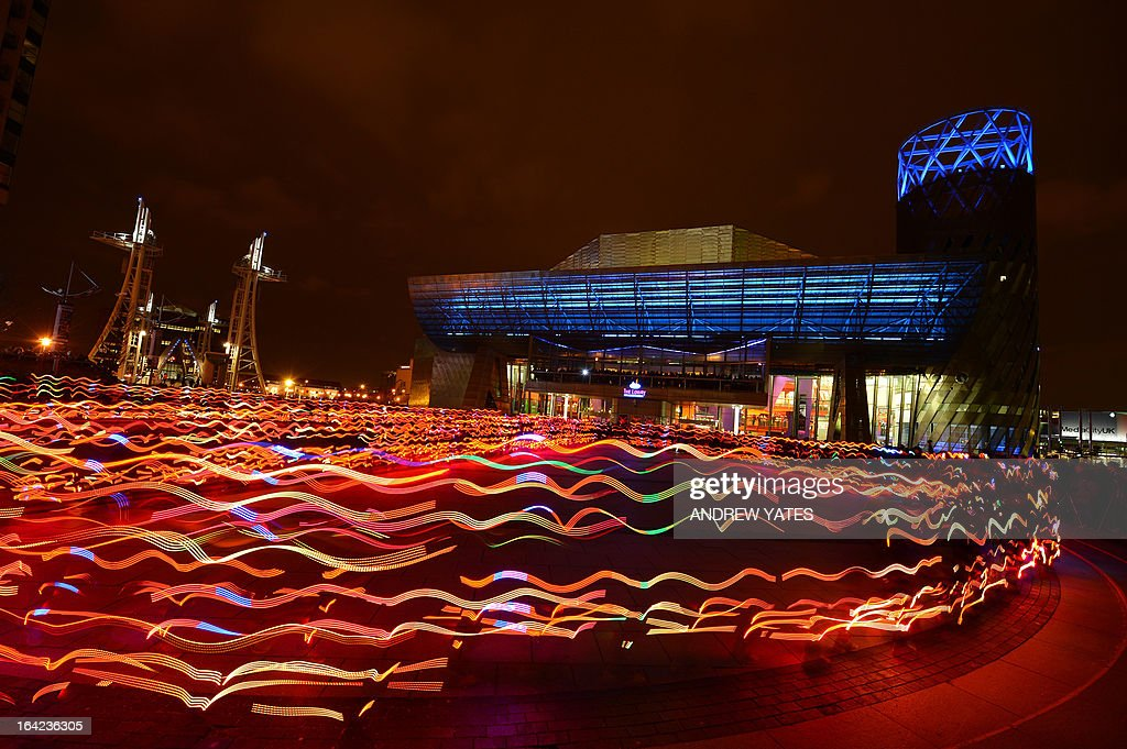 Hundreds of runners in specially commissioned and individually controlled LED light suits, create patterns of light outside the Lowry theatre in Salford Quays, Manchester, north-west England on March 21, 2013, during a performance of the Scottish arts charity NVA's 'Speed of Light' art project. AFP PHOTO/ANDREW YATES