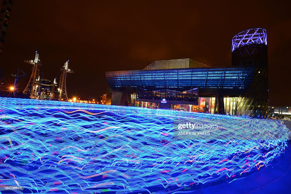 Hundreds of runners in specially commissioned and individually controlled LED light suits, create patterns of light outside the Lowry theatre in Salford Quays, Manchester, north-west England on March 21, 2013, during a performance of the Scottish arts charity NVA's 'Speed of Light' art project.