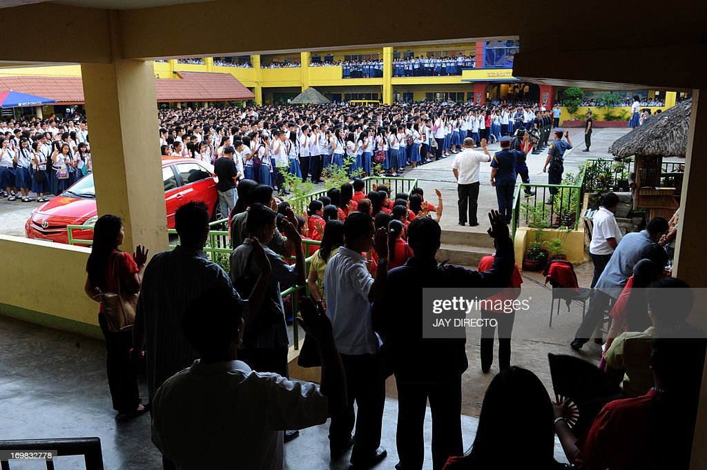 Hundreds of students join a flag ceremony to sing the national anthem at a government school in Manila on June 3, 2013. This year's school season officially opened on June 3 with up to 20 million students trooping to public elementary and high schools. AFP PHOTO / Jay DIRECTO
