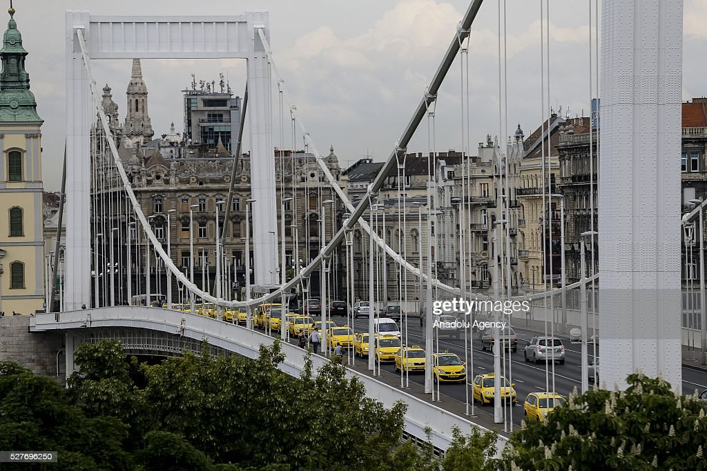 Hundreds of taxi drivers drive through the Elisabeth Bridge as they protest against the 'Uber' application, in Budapest capital city of Hungary on May 3, 2016.