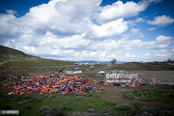 Hundreds of used life vests lie on a makeshift rubbish dump hidden in the hills above the town on March 10 2016 in Mithymna Greece The village of...