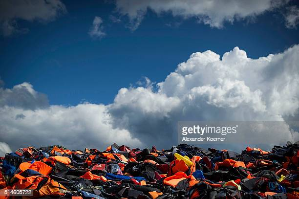 Hundreds of used life vests lie on a makeshift rubbish dump hidden in the hills above the town on March 10 2016 in Mithymna Greece Local authorities...