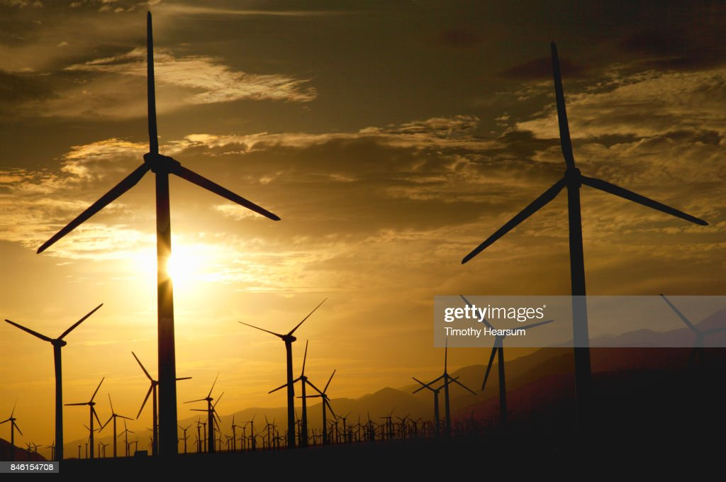 Hundreds of wind generators with mountains, sky and clouds beyond : Stock Photo
