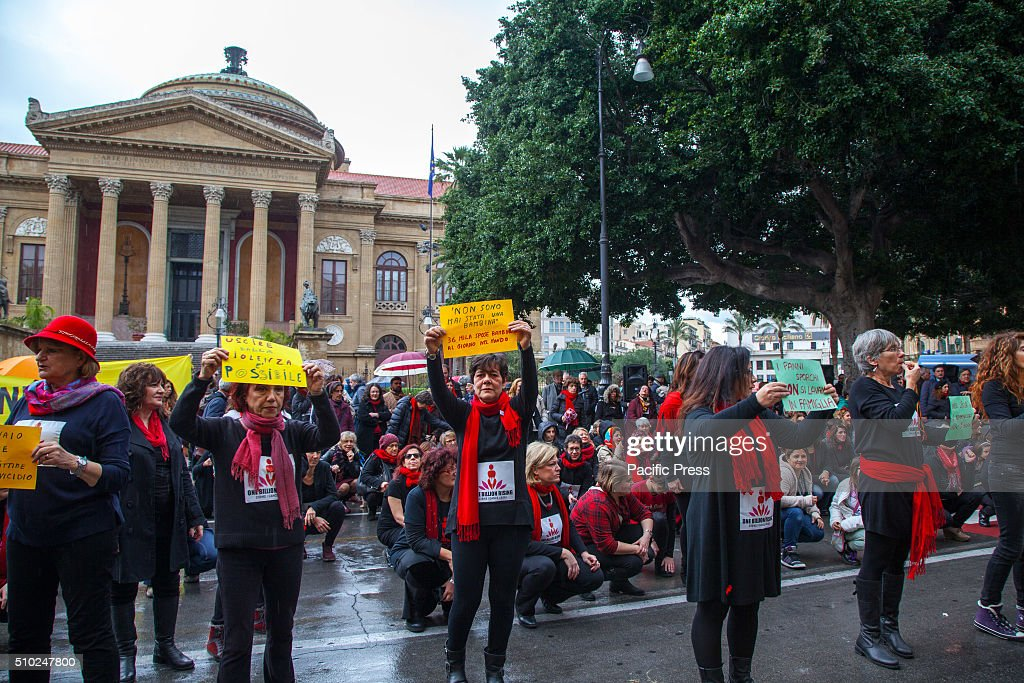 Hundreds of women wearing black with a red accessory dance during the 'One Billion Rising', where they are calling for laws not to discriminate against women and stop violence against women.