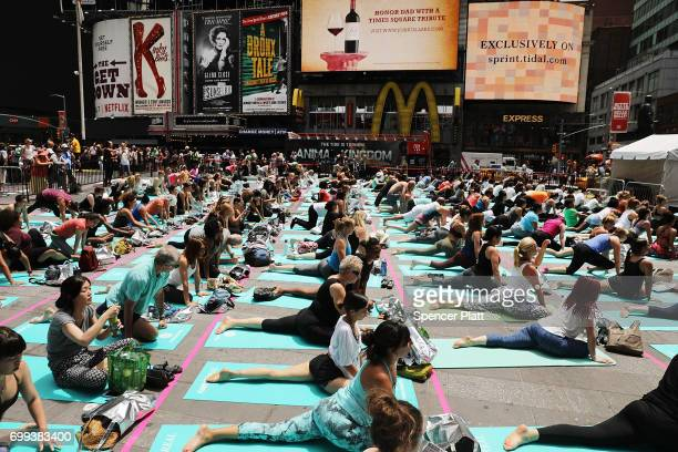 Hundreds of yoga enthusiasts participate in a mass yoga class in New York's Times Square to celebrate the summer solstice on June 21 2017 in New York...