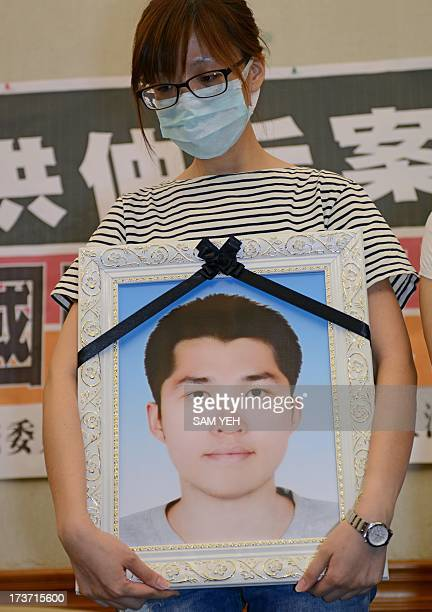 Hung Tseyung holds a portrait of her brother Hung Chungchiu during a press conference at parliament in Taipei on July 17 2013 after Hung was found by...