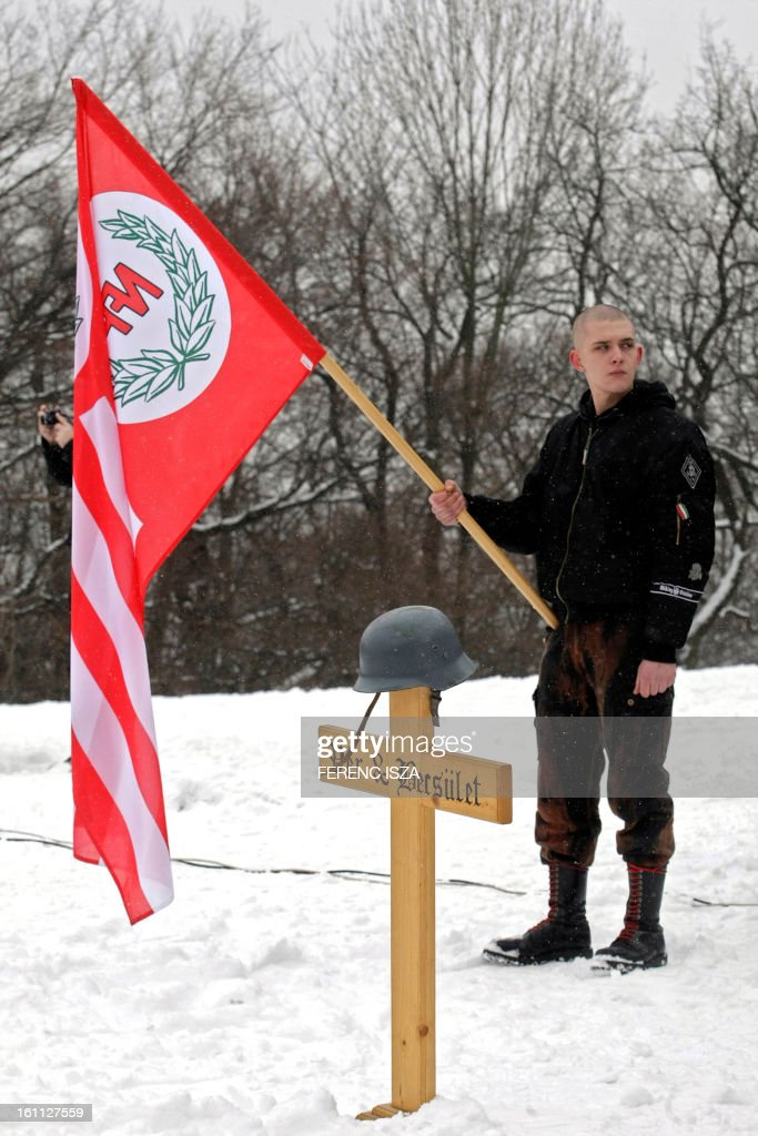 Hungarian activist of the neo-Nazi Blood and Honour group holds a flags on the 'Norma-fa' hill in Budapest on February 9, 2013. More than 500 people attended the event to commemorate the 68th anniversary of the ill-fated escape attempt of Nazi German and Hungarian soldiers from Buda Castle, which was besieged on 11 February 1945 by the Soviet Red Army at the end of World War II. Participants placed a German WWII helmet and wood cross in the snow.