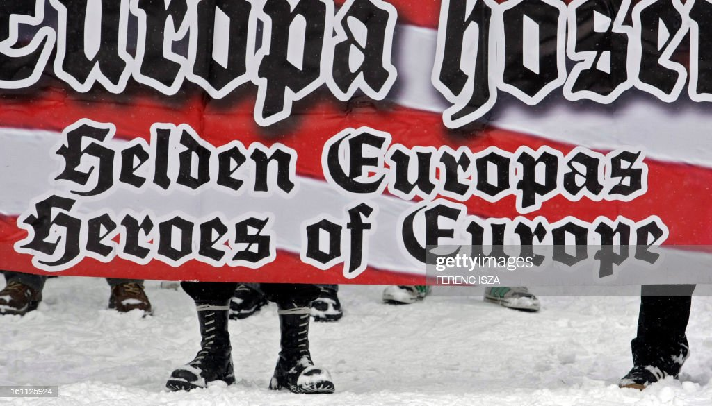 Hungarian activists of the neo-Nazi Blood and Honour group hold a banner on the 'Norma-fa' hill in Budapest on February 9, 2013. More than 500 people attended the event to commemorate the 68th anniversary of the ill-fated escape attempt of Nazi German and Hungarian soldiers from Buda Castle, which was besieged 11 February 1945 by the Soviet Red Army at the end of World War II. Participants placed a German WWII helmet and wood cross in the snow.
