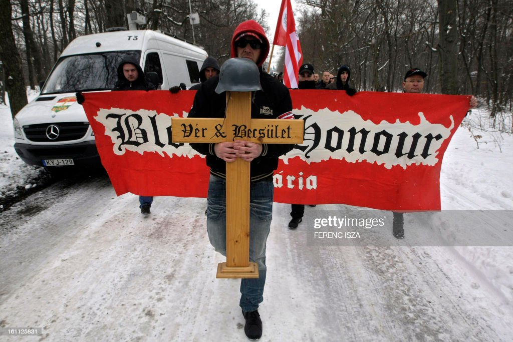 Hungarian activists of the neo-Nazi Blood and Honour group hold flags and march on the 'Norma-fa' hill in Budapest on February 9, 2013. More than 500 people attended the event to commemorate the 68th anniversary of the ill-fated escape attempt of Nazi German and Hungarian soldiers from Buda Castle, which was besieged on 11 February 1945 by the Soviet Red Army at the end of World War II. Participants placed a German WWII helmet and wood cross in the snow. AFP PHOTO / FERENC ISZA