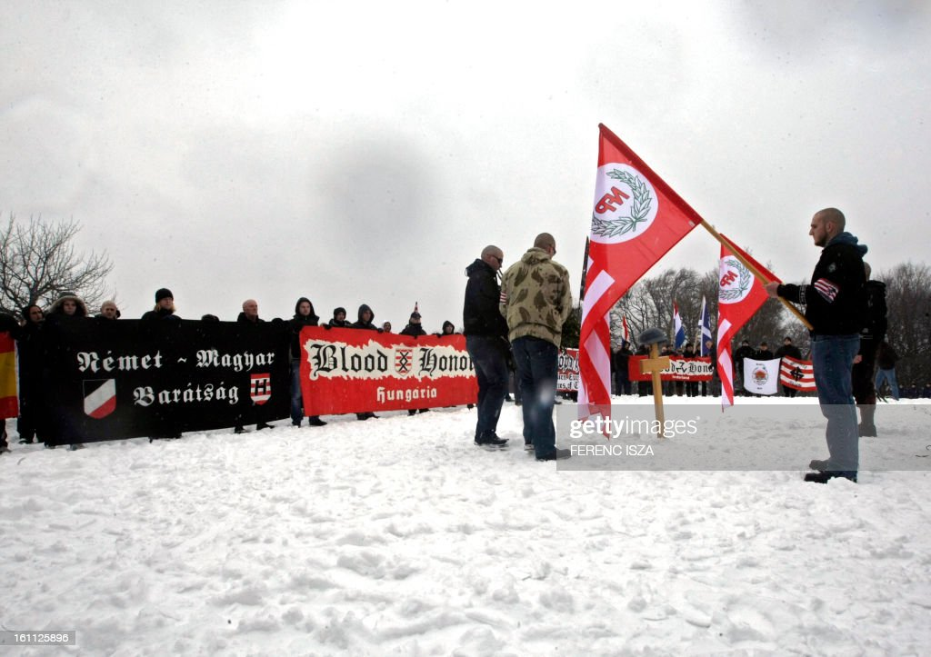 Hungarian activists of the neo-Nazi Blood and Honour group place flowers on the 'Norma-fa' hill in Budapest on February 9, 2013. More than 500 people attended the event to commemorate the 68th anniversary of the ill-fated escape attempt of Nazi German and Hungarian soldiers from Buda Castle, which was besieged on 11 February 1945 by the Soviet Red Army at the end of World War II. Participants placed a German WWII helmet and wood cross in the snow.