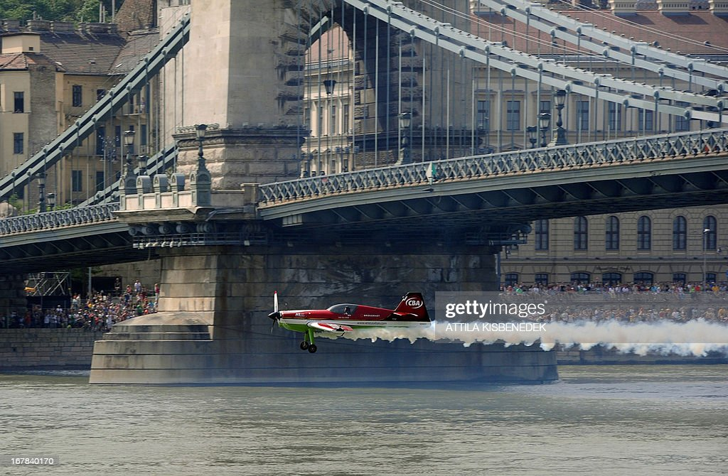 Hungarian aerobatics pilot and European champion air racer Zoltan Veres flies with his aircraft under the oldest Hungarian bridge, the 'Chain Bridge' and over the Danube River in Budapest on May 1, 2013 during an air show.