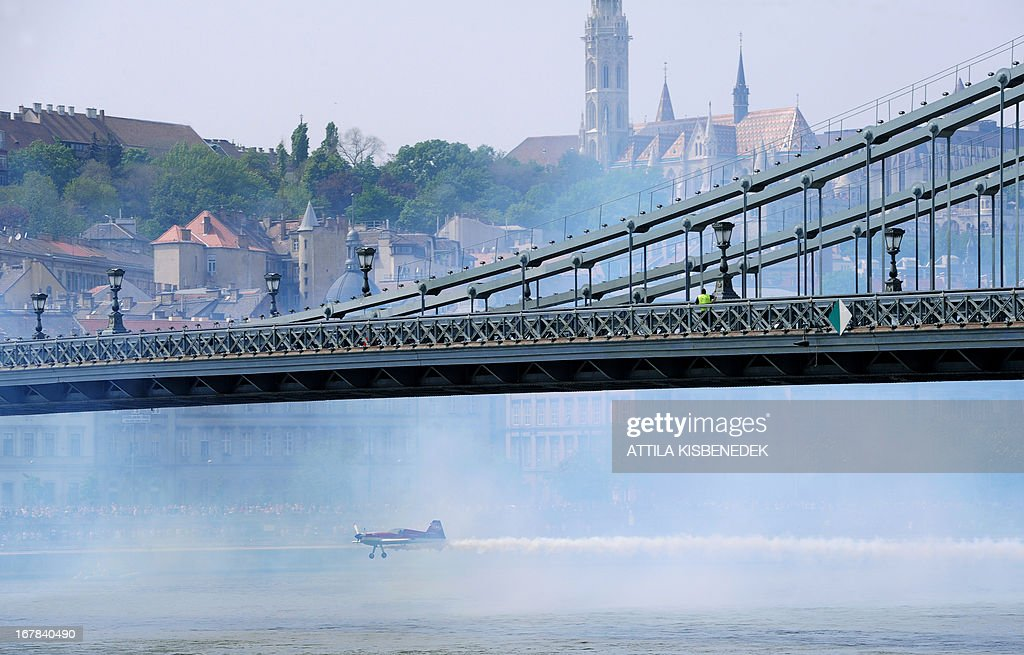 Hungarian aerobatics pilot and European champion air racer Zoltan Veres flies with his aircraft under the oldest Hungarian bridge, the 'Chain Bridge' and over the Danube River in Budapest on May 1, 2013 during an air show. AFP PHOTO / ATTILA KISBENEDEK