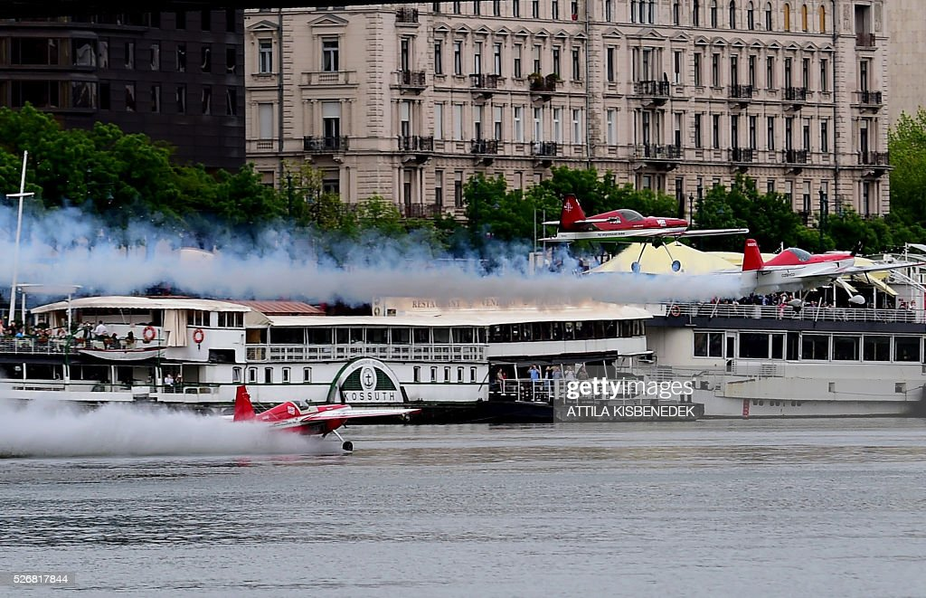 Hungarian aerobatics pilot and European champion air racer Zoltan Veres and his tean mates Australians, Jason Beamish and Larry Beamish fly in team under the oldest Hungarian bridge, the 'Chain Bridge' and over the Danube River in Budapest on May 1, 2016 during their Guinness record attempt. / AFP / ATTILA