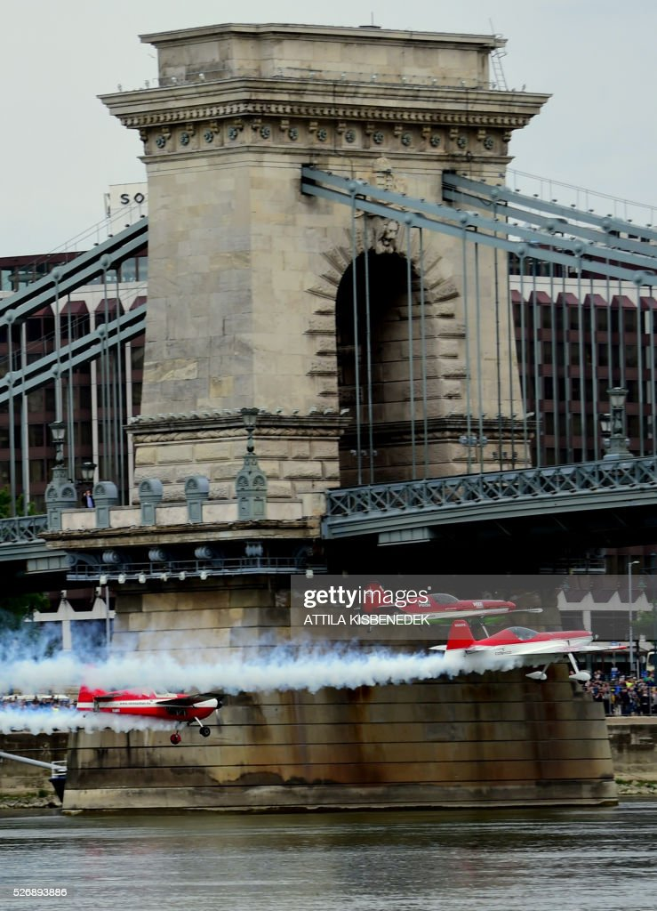 Hungarian aerobatics pilot and European champion air racer Zoltan Veres and his teammates Australians, Jason Beamish and Larry Beamish fly under the oldest Hungarian bridge, the 'Chain Bridge' and over the Danube River in Budapest on May 1, 2016 during their Guinness record attempt. / AFP / ATTILA