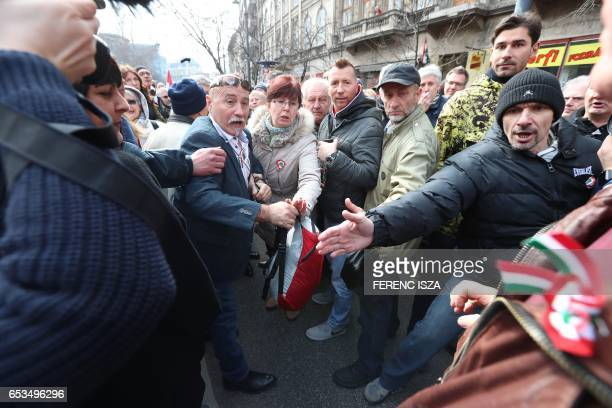 Hungarian antigovernment demonstrators whistle and clash with Orban supporters during the speech of Hungarian Prime Minister Viktor Orban at the...