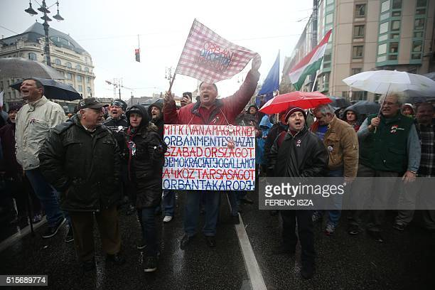Hungarian antigovernment protesters hold placards and shout slogans downtown Budapest on March 15 near the National Museum where the Hungarian Prime...