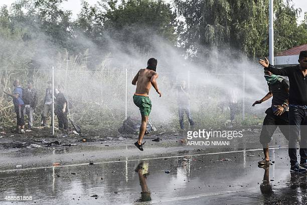 Hungarian antiriot police officers use water cannon and pepper spray to disperse migrants who try to cross the Hungarian border with Serbia near the...