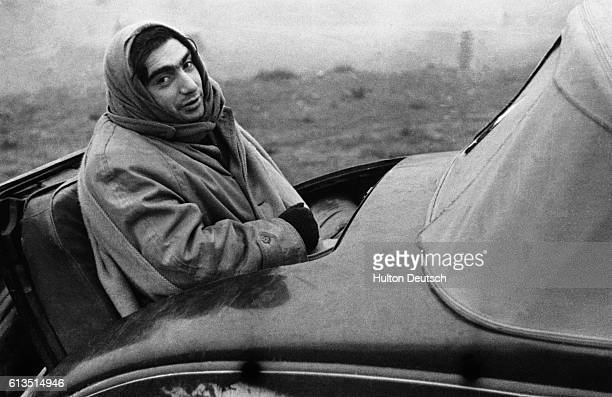 Hungarian born American photojournalist Robert Capa sitting in the rumbleseat of an automobile