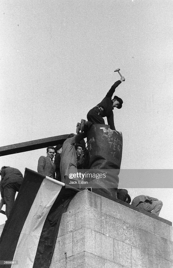 Hungarian demonstrators dismantling the boots of a giant statue of Stalin in Budapest. Original Publication: Picture Post - 8730 - Hungary's Last Battle For Freedom - pub. 1956