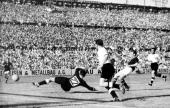Hungarian forward Nandor Hidegkuti scores the fifth goal for his team past German goalkeeper Heiner Kwiatkowski as Werner Kohlmeyer looks on during...