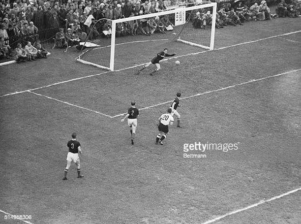 Hungarian goalie Grosits tries in vain to stop the ball shot by German forward Schaefer who scored the decisive third goal in the final game of the...