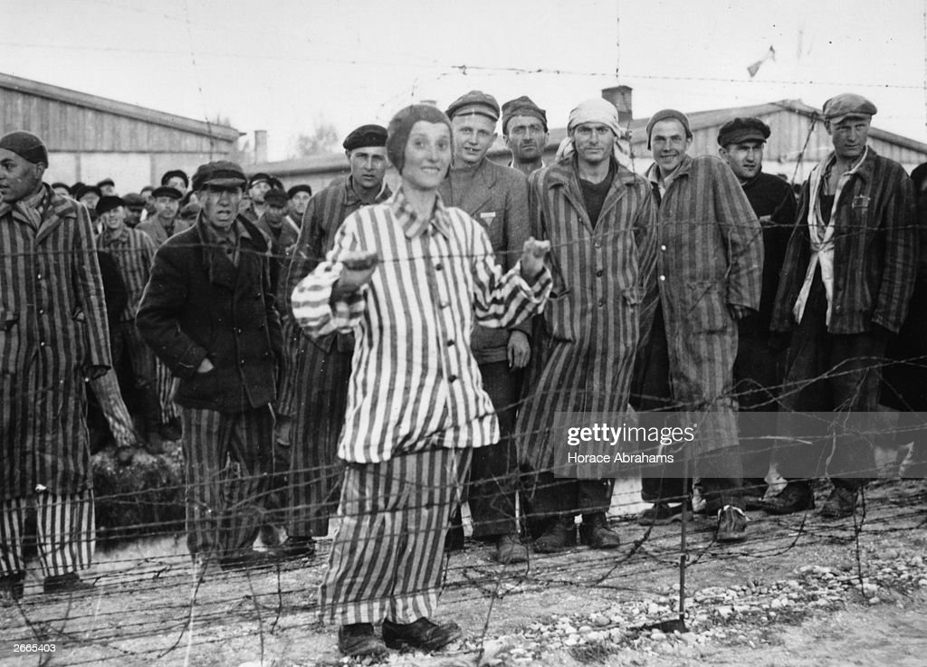 A Hungarian Jewish boy in his prison suit of blue and white stripes smiles over the barbed wire at Dachau concentraion Camp. He was expecting to be gassed in a few days time and now is saved.