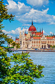 Hungarian parliament building at danube river in budapest city hungary blue sky with clouds and green tree leaves