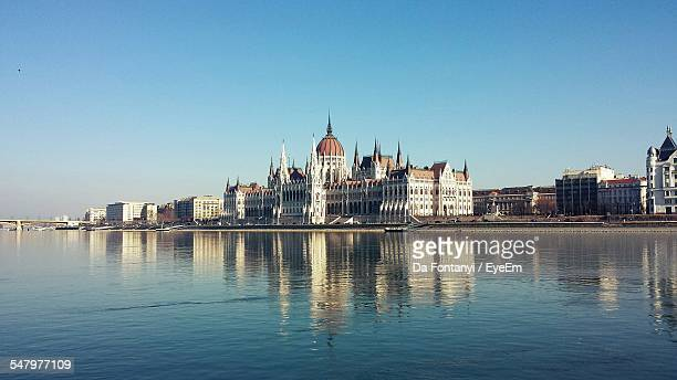 Hungarian Parliament Building With Danube River In Foreground