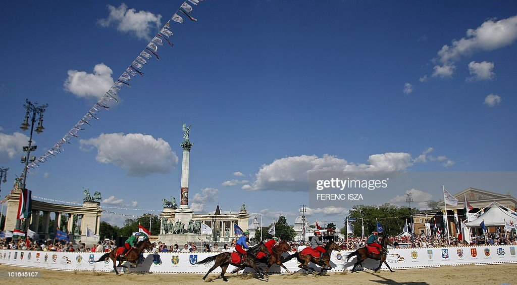 Hungarian participants compete on the Square of Heroes in Budapest on June 5, 2010 during the third National Gallop. The racers wear traditional Hungarian 'huszar' uniform and ride two and half rounds on the special sand track. Commemorating Hungary's hussar tradition, the horse races, peppered up with a charity run with local celebrities in the saddle, took place in one of the main city squares, covered by a special blend of sand for the occasion.