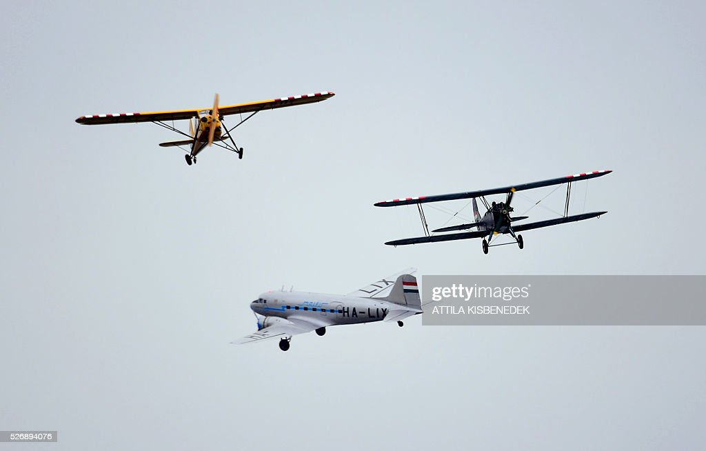 Hungarian pilots present their exercise with a R-180 (L), PO2 (R) and a Russian made Li-2 (C) air planes, over the Danube River in Budapest on May 1, 2016 during the Budapest Air Show. / AFP / ATTILA
