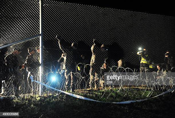 Hungarian police and soldiers close the border between Hungary and Croatia with barbed wire and a fence in Botovo on October 16 after letting one...