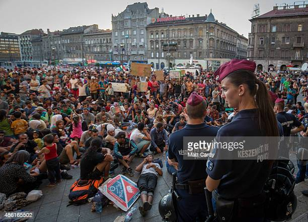 Hungarian police guard the main entrance as migrants protest outside Keleti station in central Budapest after it was closed to migrants earlier today...