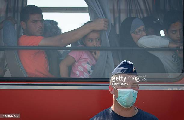 Hungarian police officer wears a face mask as migrants who have just crossed the border from Serbia into Hungary leave on a bus organised by the...