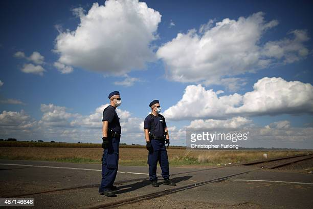 Hungarian police officers wait to greet migrants crossing the border from Serbia into Hungary along the railway tracks close to the village of Roszke...