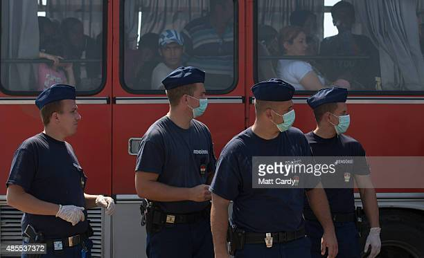 Hungarian police officers wear face masks as migrants who have just crossed the border from Serbia into Hungary leave on a bus organised by the...