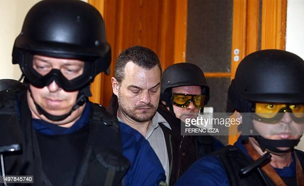 Hungarian policemen escort British citizen Simon Jonathan K to a court room at Budapest Capital Court in Budapest on November 19 after he has been...