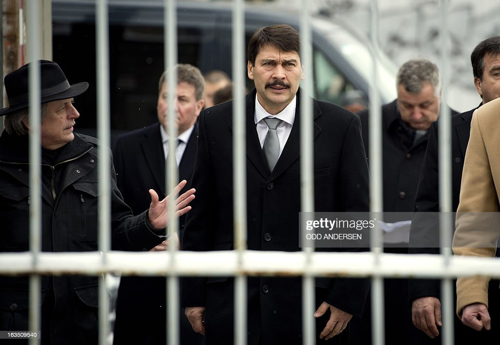 Hungarian President Janos Ader (C) arrives at the gate of the former East German secret police (STASI) prison in Hohenschoenhausen, Berlin on March 11, 2013, during his state visit to Germany . The prison is a memorial site since 1994.