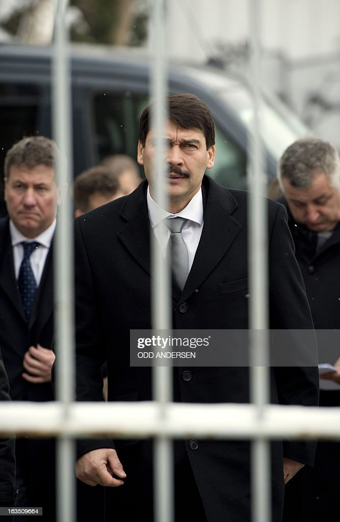 Hungarian President Janos Ader (C) is seen through the railings of a gate as he arrives at the former East German secret police (STASI) prison in Hohenschoenhausen, Berlin on March 11, 2013, during his state visit to Germany . The prison is a memorial site since 1994.
