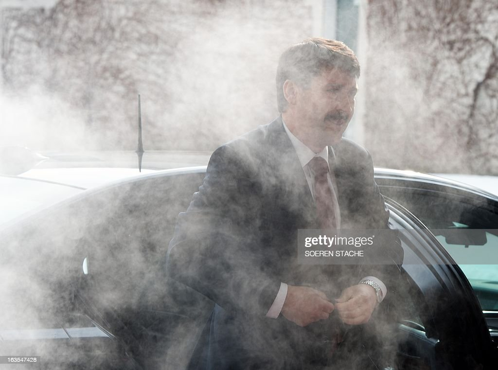 Hungarian President Janos Ader is surrounded by a cloud of exhaust emissions as he gets off his car to visit the German Chancellor on March 12, 2013 at the Chancellery in Berlin.