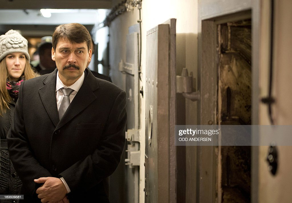 Hungarian President Janos Ader stands next to the open door of a bunker cell of the former East German secret police (STASI) prison in Hohenschoenhausen, Berlin on March 11, 2013, during his state visit to Germany . The prison is a memorial site since 1994.