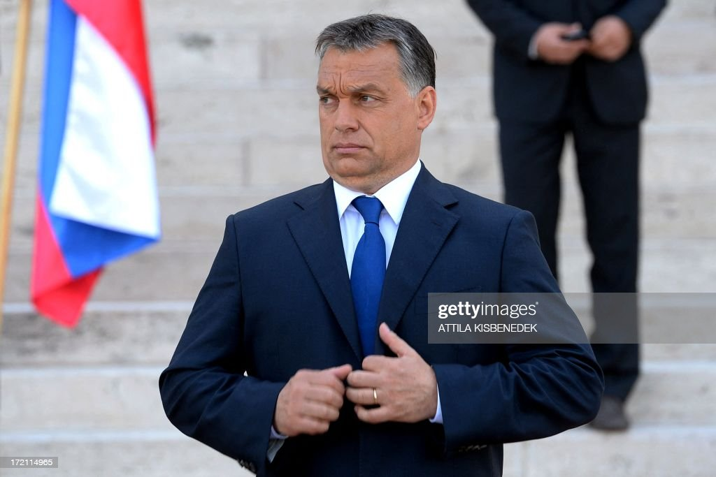Hungarian Prime Minister Viktor Orban adjusts his jacket while waiting before his Slovakian counterpart's arrival in front of the parliament building in central Budapest on July 2, 2013. Orban is to meet with Robert Fico for his one-day working visit. AFP PHOTO / ATTILA KISBENEDEK