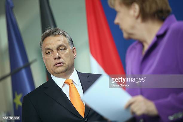 Hungarian Prime Minister Viktor Orban and German Chancellor Angela Merkel arrive to speak to the media prior to talks at the Chancellery on May 8...