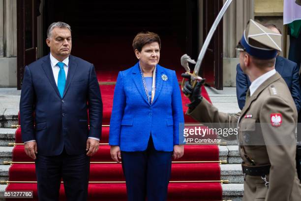 Hungarian Prime Minister Viktor Orban and his Polish counterpart Beata Szydlo review the guard of honour during a welcoming ceremony prior to their...