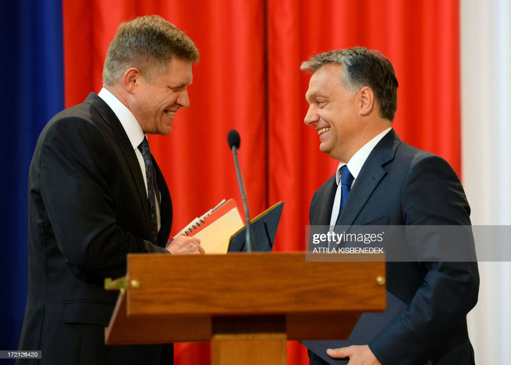 Hungarian Prime Minister Viktor Orban (R) and his Slovakian counterpart Robert Fico (L) chat in Delegation Hall of the parliament building in central Budapest on July 2, 2013 after their joint press conference. Orban meets with Fico for his one-day working visit. AFP PHOTO / ATTILA KISBENEDEK