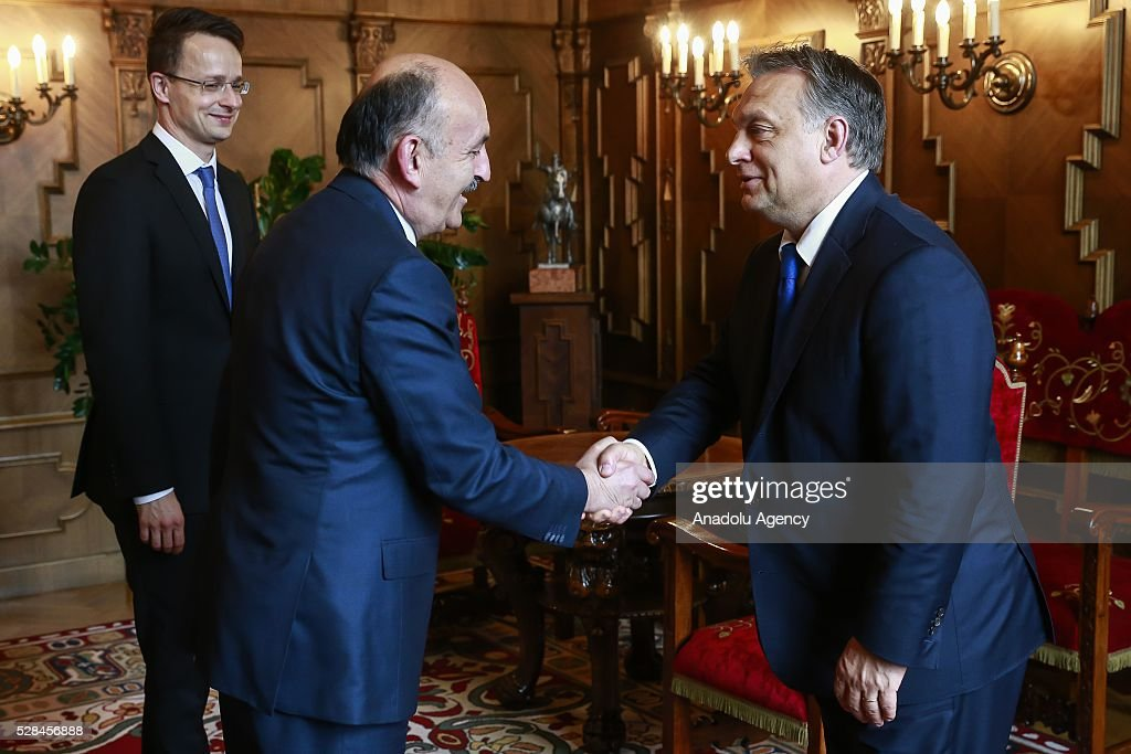 Hungarian Prime Minister Viktor Orban (R) and Turkish Health Minister Mehmet Muezzinoglu (C) shake hands in Budapest, Hungary on May 2, 2016.