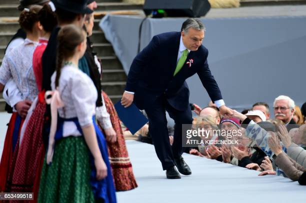 Hungarian Prime Minister Viktor Orban is welcomed by participants prior to his speech in front of the National Museum of Budapest on March 15 2017...