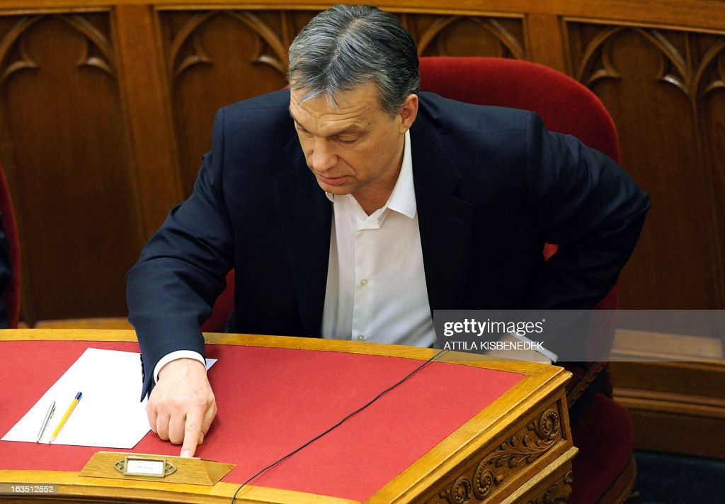 Hungarian Prime Minister Viktor Orban pushes the button to vote during a parliamentary session on March 11, 2013 in Budapest. The Hungarian Parliament adopted the fourth modification of the basic law with 265 votes in favour, 11 against and 33 member abstaining. The changes, which have also sparked protests in Budapest, include a curb on the power of the constitutional court and reintroduce controversial measures rendered void by the court in recent months. AFP PHOTO / ATTILA KISBENEDEK